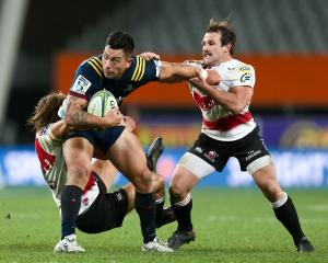 Thompson of the Highlanders is tackled by Andries Coetzee and Nic Groom of the Lions at Forsyth...
