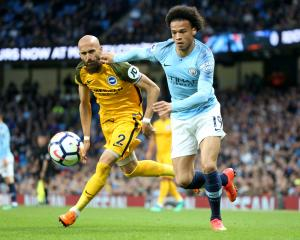 Leroy Sane of Manchester City is challenged by Bruno Saltor of Brighton and Hove Albion in a...
