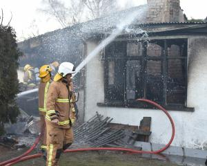 Firefighters work to extinguish a fire that gutted a home in Nottage St, Middlemarch, yesterday...