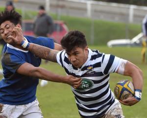 Otago Boys' High School flanker Jesse Va'afusuaga fends off Southland Boys' High School centre...