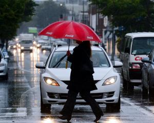 A pedestrian scurries across Castle St during a downpour in Dunedin. Photo: Gerard O'Brien