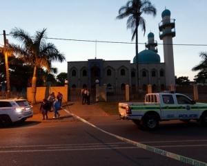 Police investigators collect evidence at a mosque where three men where attacked in Ottawa, South...