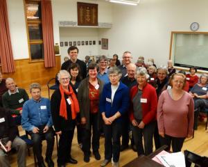 Choir director David Burchell (standing back left) gathers with some of the 30 members (also...