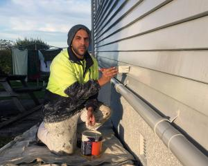 Dunedin Housing Maintenance Contractors brush hand and former refugee Mohammed Ali paints a state...