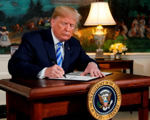 US. President Donald Trump signs a proclamation declaring his intention to withdraw from the...