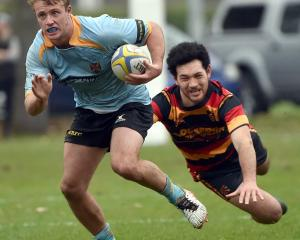 University loose forward Jack McHugh evades the tackle of Zingari-Richmond first five-eighth...
