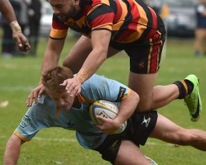 University A flanker Jack Mchugh is tackled by Zingari 2nd five Keenan Masina during the premier...