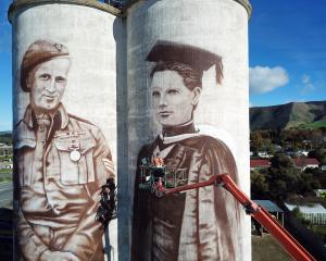 Waimate artist Bill Scott works on murals on grain silos at Transport Waimate's Queens St yard....