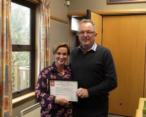 Kate Rive receiving a certificate of appreciation from Detective Senior Sergeant Malcolm Inglis. ...