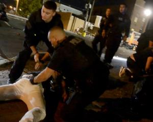 Police officers are seen detaining a man after the shooting. Photo: Facebook/ Edward Forchion via...