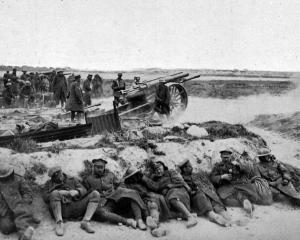 British soldiers take a rest while their artillery is in action pounding the German lines. —...