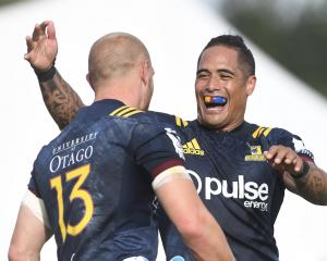 Highlanders halfback Aaron Smith is full of joy after centre Matt Faddes scores a try in a pre...