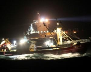 Dutch fishing boat OUDDORP 6 (front) and a Dutch navy ship take part in rescue efforts after a...