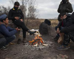 A group of young migrants warm themselves near a campfire on an industrial estate on March 5,...