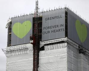 New hoarding covers the top of the Grenfell Tower to mark the first anniversary of the fire that...
