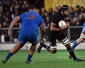 Jackson Hemopo runs the ball up while watched by French prop tighthead Uini Atonui. Photo: Peter...
