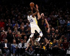 Golden State Warriors forward Kevin Durant shoots over Cleveland Cavaliers forward Kevin Love...