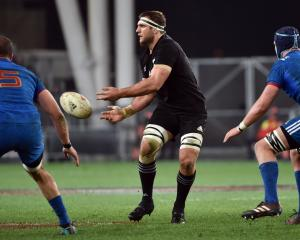 All Blacks Luke Whitelock passes the ball while watched by French locks Yoann Maestri (left) and...