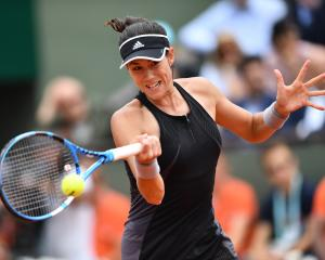 Gabine Muguruza plays a forehand during her quarterfinal against Maria Sharapova at the French...