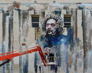 Street artist Tyler Kennedy Stent applies sealant to his mural of Ralph Hotere in Carroll St,...