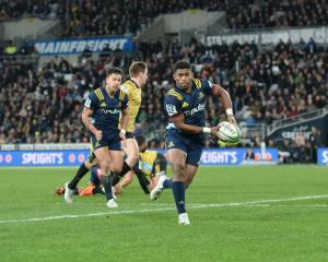 Highlanders wing Waisake Naholo makes a burst supported by flanker Rob Thompson (left)....