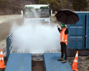 Logan Point Quarry manager Joe Hunter directs a truck through the quarry's new spray truck wash....