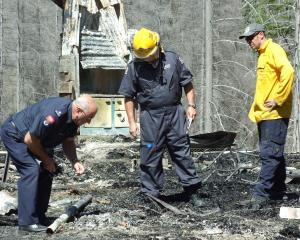 Police and firefighters inspect the scene of the Mt Aurum homestead fire at Skippers, near...