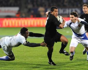 All Black fullback Mils Muliaina gets past French loosie Fulgence Ouedraogo and winger Vincent...