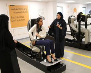 A driving instructor (R) explains seat bells to trainees Amira Abdulgader and Maria Al-Faraj (C)...
