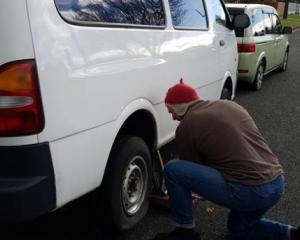 Wayne Roycroft changing the slashed tyre of his Kia Pregio. The Nissan Lafesta parked in front...
