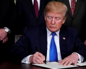 US President Donald Trump signs a memorandum on intellectual property tariffs on high-tech goods...