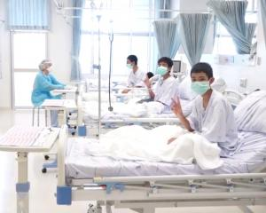 A screen grab shows boys rescued from the Thai cave wearing mask and resting in a hospital in...