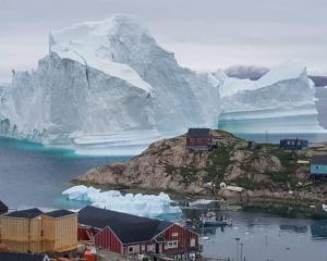 The iceberg towers over the village of Innarsuit, on the northwestern Greenlandic coast. Photo:...