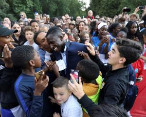 France defender Benjamin Mendy is congratulated by supporters during a reception at the Elysee...