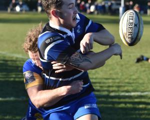 Kaikorai winger Jordan McEntee is tackled by Taieri outside back Mitchell Scott at Bishopscourt...