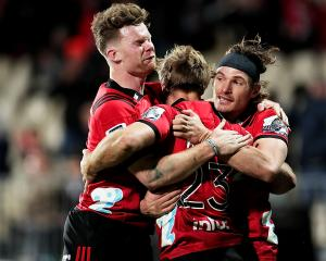 Braydon Ennor (C) of the Crusaders celebrates with his team mates Mitchell Drummon (L) and George...