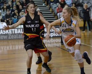 Otago Gold Rush's Zoe Richards looks ahead while Waikato'sNatasha Lenden comes across to shut...