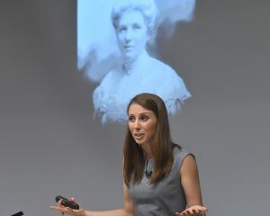Writer, musician and activist Lizzie Marvelly, in front of a photo of New Zealand suffragette...