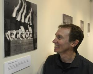 Associate Prof Chris Button admires a photo from the Movement Through Time exhibition at Hocken...