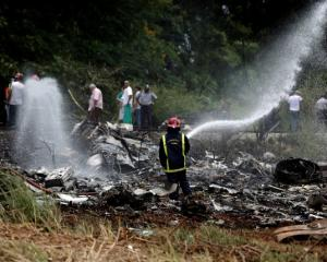 A firefighter works in the wreckage of a Boeing 737 plane that crashed in the agricultural area...