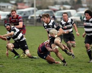 Crescent loose forward Andrew Carruthers is tackled by Clutha Valley's Crewze Kingi during a ...
