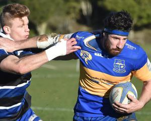 Taieri flanker Josh Brown attempts to fend off Kaikorai fullback Ben Miller at Bishopscourt on...