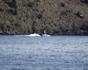 A jet ski helps conduct the search for the missing helicopter and pilot on Lake Wanaka. Photo:...