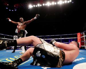 New Zealander Joseph Parker sprawls on the ground after being  knocked down by British boxer...