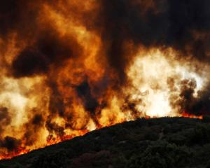 Wind-driven flames roll over a hill towards homes during the River Fire (Mendocino Complex) near...