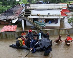 Rescue workers evacuate people from flooded areas on the outskirts of Kochi in India. Photo:...