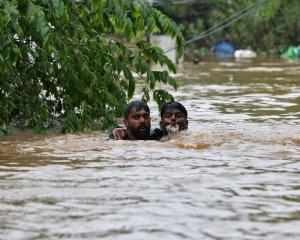 A man helps another through floodwaters on the outskirts of Kochi in the state of Kerala. Photo:...