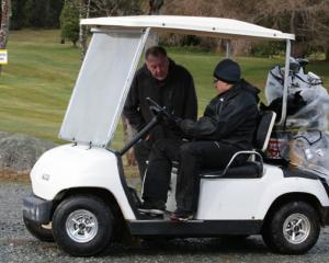 ING 7301:  Glen Donovan-Manager of Fiordland Hotel (in cart) discusses with his golf partner,...