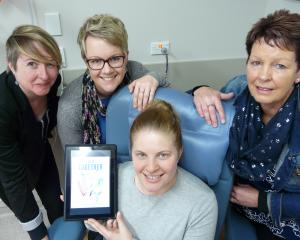 Demonstrating one of three new tablets, loaded with new cancer survivor magazine In It Together,...