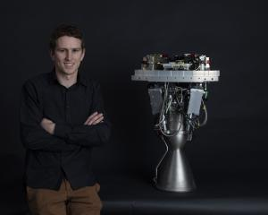 Lachlan Matchett with the engine he helped design for Rocket Lab's Electron rocket. Photo: Rocket...